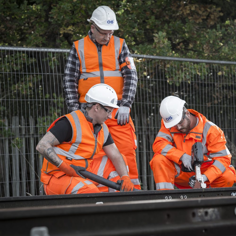 Three men with tools working on a rail track