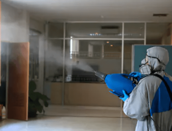 A person in a suit disinfecting a room