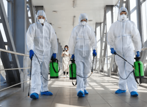 Three people in suits disinfecting in a building